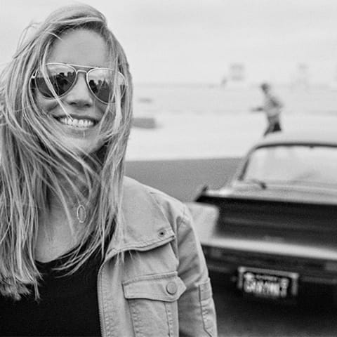 Woman in sunglasses in foreground with Porsche 911 964 behind