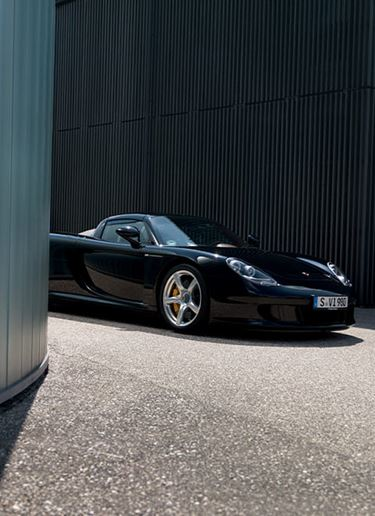 Nose of Carrera GT peeking out from behind buildings