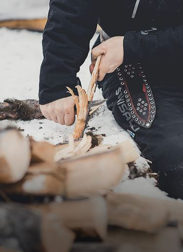 Person whittling stick in the snow with a puukko knife